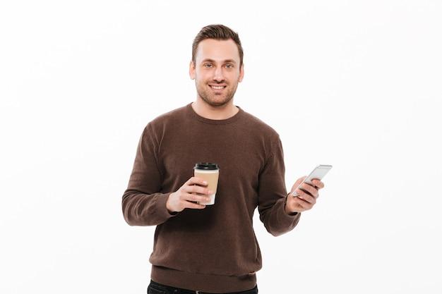 Rozochocony młody człowiek pije kawę i gawędzi