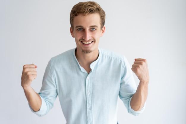 Rozochocony młody człowiek pompuje pięści i patrzeje kamerę
