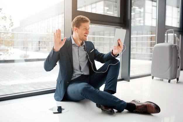 Rozochocony młody człowiek siedzi na podłoga i powitaniu. macha ahnd. młody człowiek ma rozmowę wideo. on używa słuchawek. facet liść walizka i telefon z biletami na podłodze.