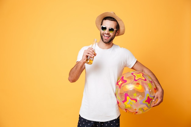 Rozochocony młody człowiek trzyma piwo i plażową piłkę