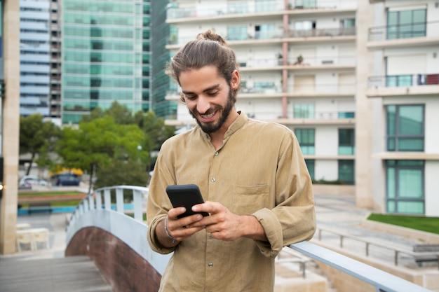 Rozochocony młody człowiek używa smartphone