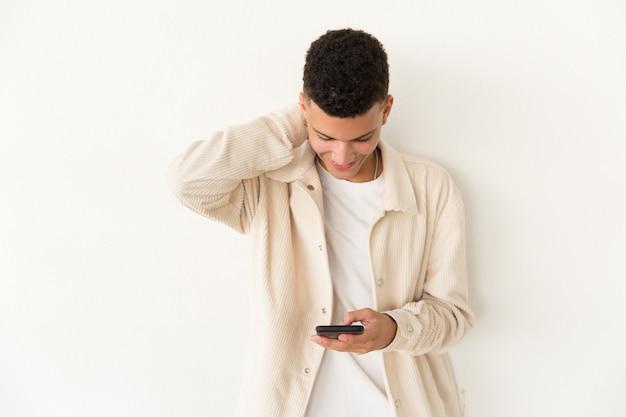 Rozochocony młody człowiek używa telefon komórkowego