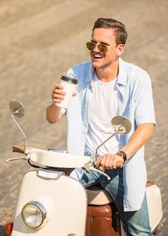 Rozochocony młody człowiek w okularach przeciwsłonecznych siedzi na hulajnoga.