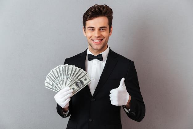 Rozochocony młody kelner pokazuje aprobaty trzyma pieniądze.