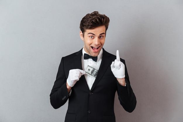 Rozochocony młody kelner trzyma pieniądze pomysłu wskazywać.