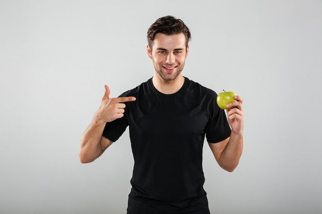 Rozochocony młody sporta mężczyzna mienia jabłko i wskazywać.