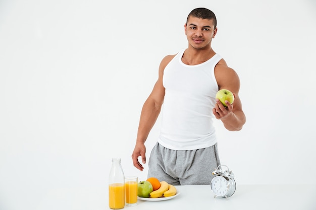 Rozochocony młody sportowa mienia jabłko.