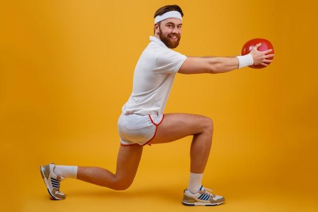 Rozochocony młody sportowiec trzyma piłkę robi ćwiczeniom sportowym.