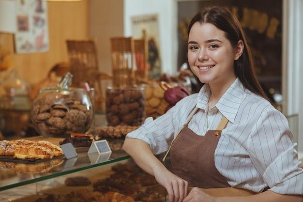 Rozochocony młody żeński piekarniany ono uśmiecha się i pracuje przy piekarnia sklepem