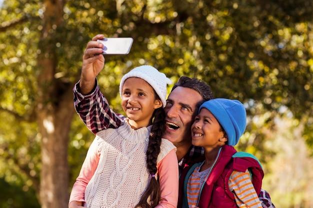 Rozochocony ojciec bierze selfie z dziećmi