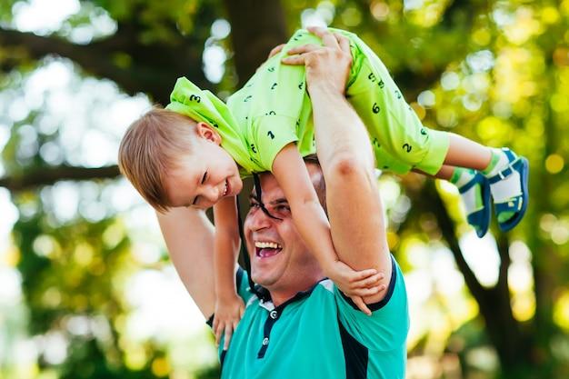 Rozochocony ojciec ma zabawę z jego małym synem w parku.