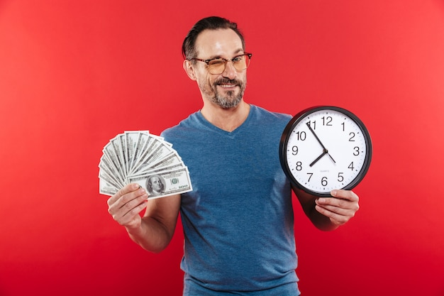 Rozochocony pozytywny mężczyzna trzyma pieniądze i zegar w kolorowych okularach przeciwsłonecznych podczas gdy mrugający.