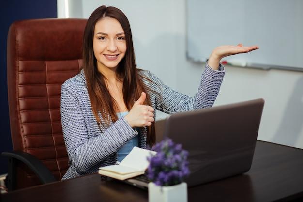 Rozochocony pracownik pisać na maszynie na laptopie i patrzeje daleko od z jaskrawym uśmiechem. ona siedzi przy biurku w biurze. portret