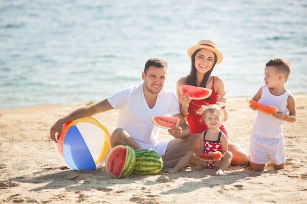 Rozochocony rodzinny łasowanie arbuz na plaży. małe dzieci i ich rodzice bawią się na brzegu morza. radosna rodzina nad morzem