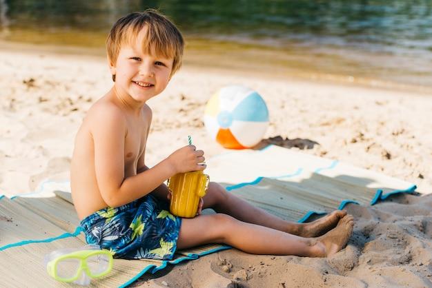Rozochocony śliczny dzieciak ono uśmiecha się na wybrzeżu