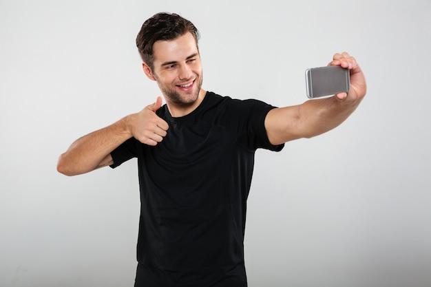 Rozochocony sportowiec robi selfie telefonem komórkowym pokazuje aprobaty.