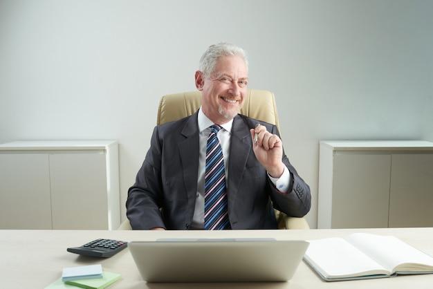 Rozochocony starszy biznesmen pozuje dla fotografii