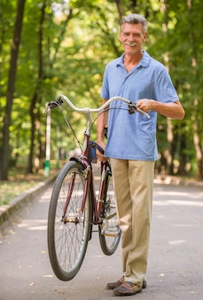 Rozochocony starszy mężczyzna z bicyklem w parku.