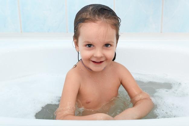 Rozochocony szczęśliwy berbecia dziecko bierze skąpanie. małe dziecko w wannie, relaks w ciepłej wodzie.