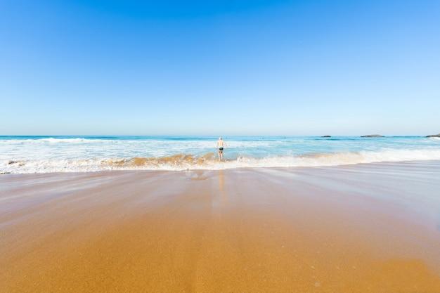 Rozochocony szczęśliwy męski oszukiwanie i żartować jak dziecko w morzu.