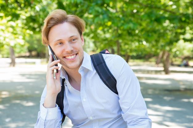 Rozochocony szczęśliwy uczeń z plecakiem gawędzi na telefonie