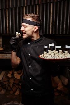Rozochocony szef kuchni pozuje z porcją khinkali. gruzińska tradycyjna kuchnia narodowa. proces gotowania. kuchnia. koncepcja żywności.