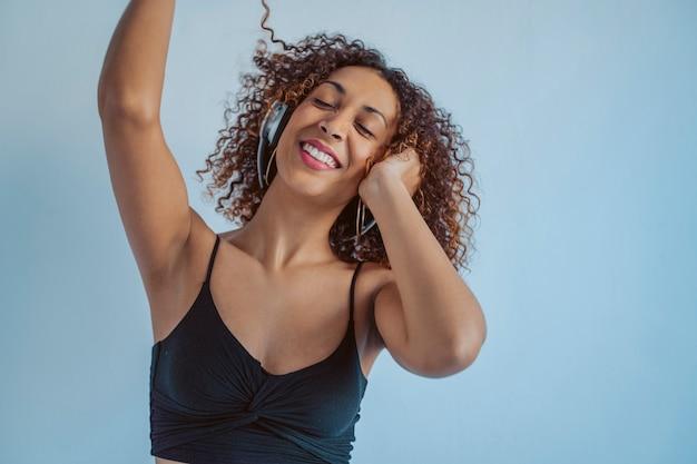 Rozochocony tancerza amerykanina afrykańskiego pochodzenia słucha muzyka z bezprzewodowymi hełmofonami. młoda kobieta afro tańcząca w rytm czarnej muzyki.