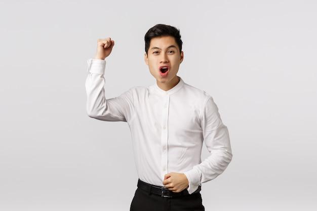Rozochocony uśmiechnięty azjatykci młody przedsiębiorca rozwesela up z białą koszula