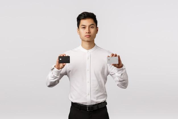 Rozochocony uśmiechnięty azjatykci młody przedsiębiorca trzyma kredytowe karty z białą koszulową