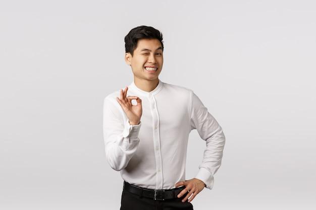 Rozochocony uśmiechnięty azjatykci młody przedsiębiorca z białą koszula z zadowalającym gestem