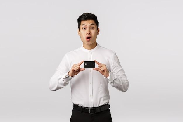 Rozochocony uśmiechnięty azjatykci młody przedsiębiorca z białą koszulową mienie wizytówką