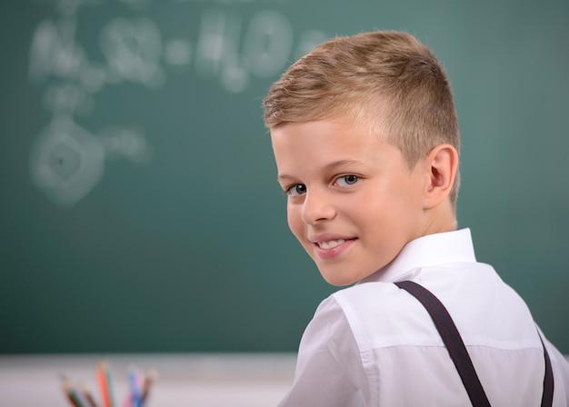 Rozochocony uśmiechnięty dziecko przy blackboard.
