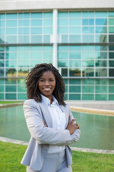 Rozochocony uśmiechnięty żeński profesjonalista pozuje blisko biura