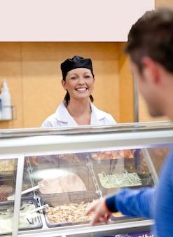 Rozochocony żeński piekarniany słuchanie uczeń w kolejce bufet