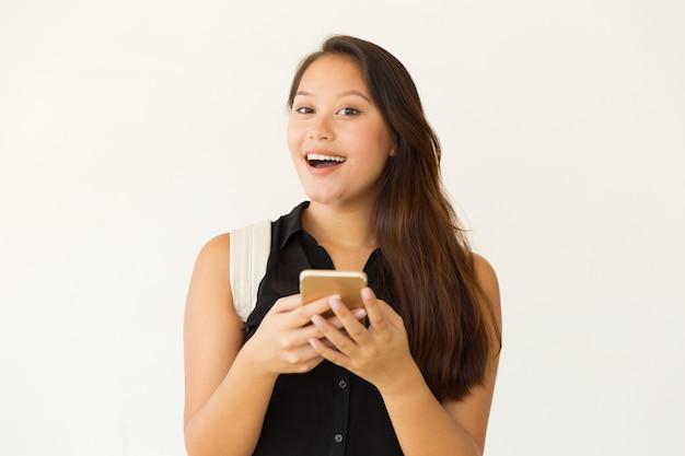 Rozochocony żeński uczeń używa smartphone