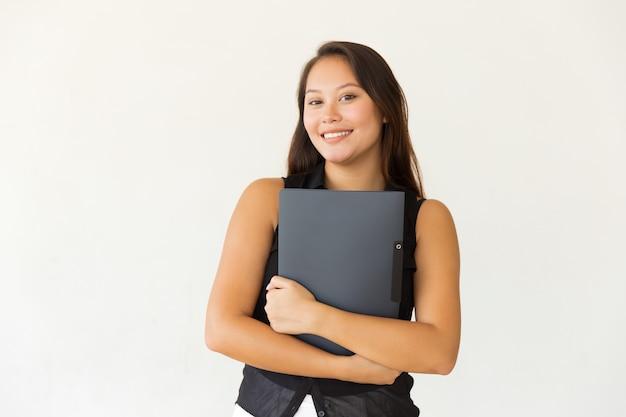 Rozochocony żeński uczeń z skoroszytowy ono uśmiecha się przy kamerą