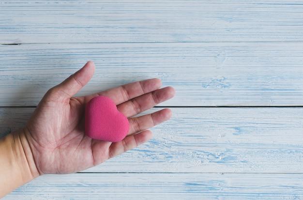 Różowa bańka w kształcie serca w dłoni azjatyckiego mężczyzny w pastelowym odcieniu, widok z góry