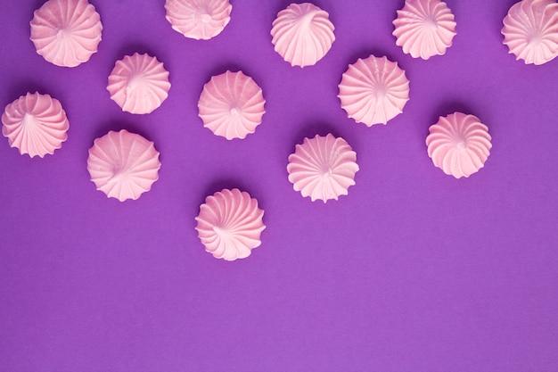 Różowa beza na fioletowej powierzchni. widok z góry. skopiuj miejsce.