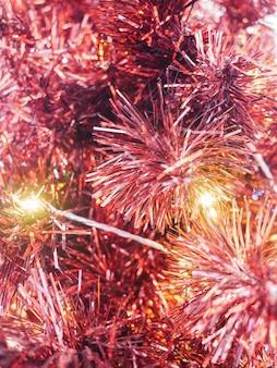 Różowa błyszcząca girlanda bożonarodzeniowa i ciepłe lampki wróżki