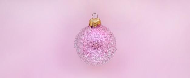 Różowa bombka z kilkoma guzkami na różowym tle minimalne świąteczne miejsce na tekst