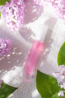 Różowa butelka perfum i światło i cień gałęzi bzu koncepcja perfum reklamowych