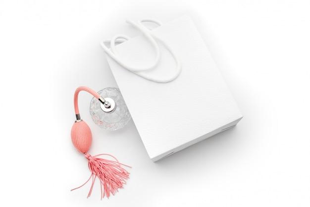 Różowa butelka perfum z białą papierową torbą na zakupy. perfumy, kosmetyki, kolekcja zapachów. temat sprzedaży, mody, zakupów i reklamy.