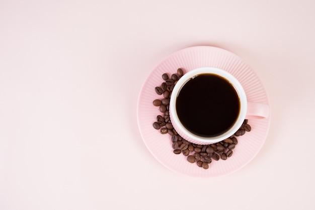 Różowa filiżanka czarna kawa na różowym pastelowym tle, monochrom, odgórny widok
