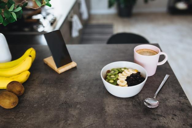 Różowa filiżanka kawy, miska z posiekanymi owocami tropikalnymi kiwi i bananem, jagodami, łyżką i telefonem komórkowym na blacie barowym w stylowej kuchni na poddaszu.