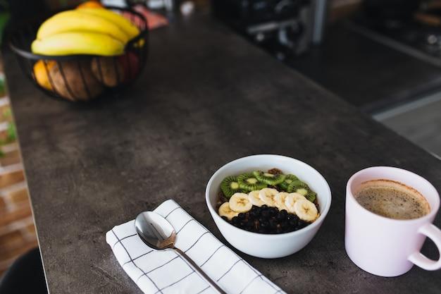 Różowa filiżanka kawy, miska z posiekanymi owocami tropikalnymi kiwi i bananem, jagody, łyżka na blacie barowym w stylowej loftowej kuchni.