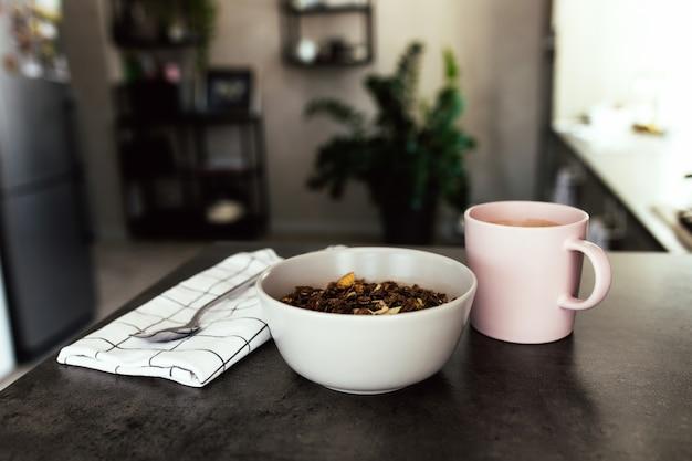 Różowa filiżanka kawy, miska z posiekanymi owocami tropikalnymi kiwi i bananem, jagody, łyżka na ręczniku na blacie barowym w stylowej loftowej kuchni. niewyraźne tło. wysokiej jakości zdjęcie