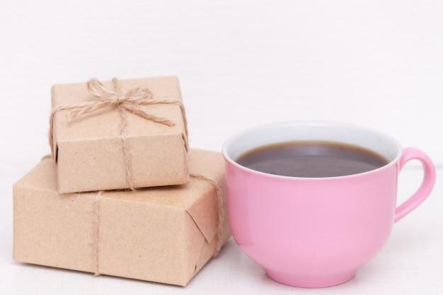 Różowa filiżanka kawy z pressents. dzień dobry dla kobiety, żony, córki, dziewczyny, matki.