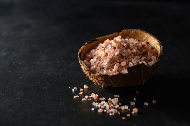 Różowa gruba sól himalajska w kokosowej misce na ciemnoszarym tle