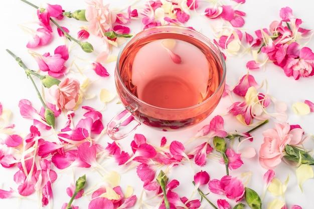 Różowa herbata kwiatowa z płatkami goździków. gorący napój różany w szklanym kubku