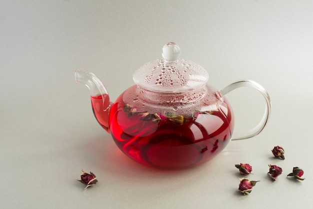 Różowa herbata z różami w szklanym imbryku. zbliżenie. skopiuj miejsce.